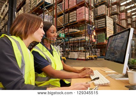 Two female colleagues working in the office of a warehouse
