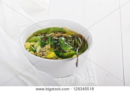 Green minestrone with a lot of vegetables and pasta