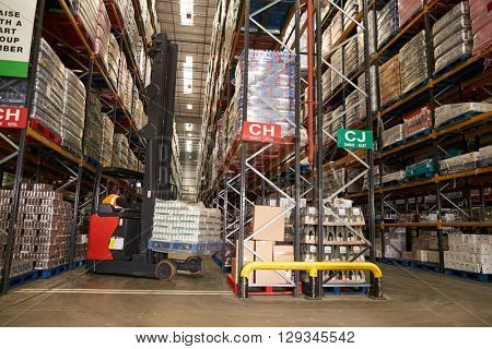Lowering stock in a distribution warehouse using aisle truck