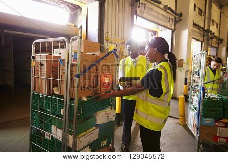 Warehouse manager oversees a woman preparing a delivery