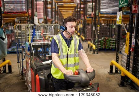 Man driving a tow tractor through a distribution warehouse