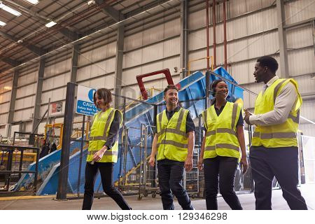 Four coworkers talk as they walk in an industrial interior