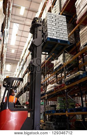An aisle truck truck moving stock in a warehouse, vertical