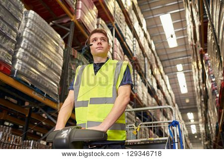 Man driving a tow tractor in a distribution warehouse