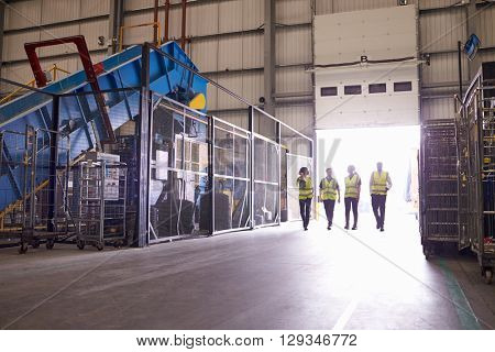 Four coworkers walking in an industrial interior, wide view