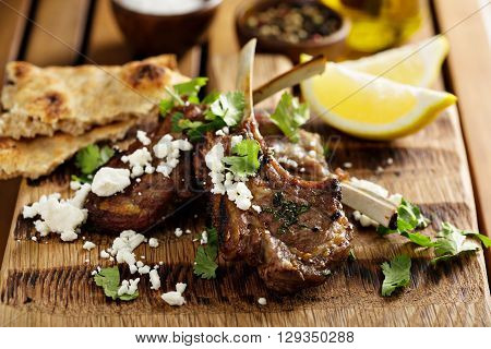 Lamb chops with herbs, lemon, pita bread and feta
