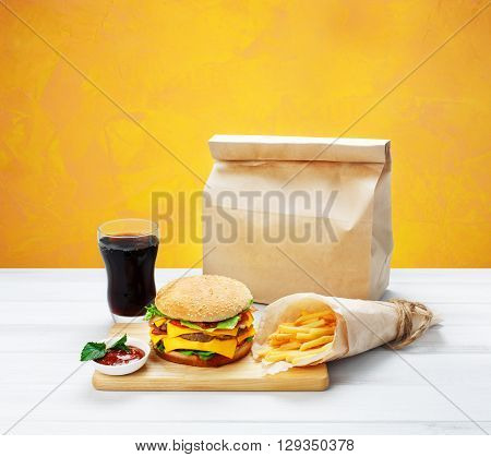 Fast food. Brown wrapping paper package with copyspace. Hamburger, potato fries, cola drink. Takeaway food. Wrapped French fries, packaging, Cola glass, tomato sauce, double cheese hamburger at wood.