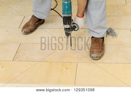 Laying plywood on the floor. Worker drill floor to fix a plywood.