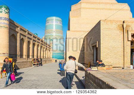 Khiva Uzbekistan - Aprilr 15 2014: Local people in the country center with the Kalta Minor minaret and Muhammad Amin Khan Madrassah