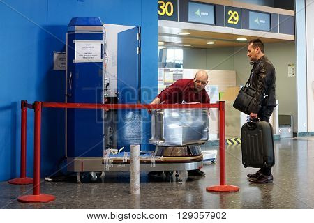 VALENCIA, SPAIN - MAY 5, 2016: An airline passenger having his luggage wrapped in industrial strength cling film. Wrapping your luggage in cling film can provide peace of mind ahead of your journey.