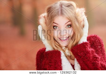 Portrait of pretty smiling fashionable woman in fall forest park. Happy gorgeous young girl in earmuffs and sweater pullover. Autumn winter fashion.
