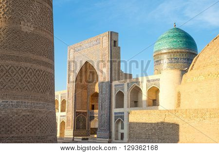 Uzbekistan Bukhara the Mir-i-Arab madrassah with the Kalon minaret on the left poster