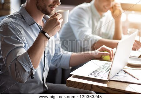 Get some energy. Pleasant delighted handsome bearded man sitting at the table and drinking coffee while his colleague talking on the cellphone in  the background