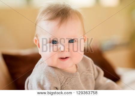 Closeup portrait of smiling little child with blond hair and blue eyes wearing knitted sweater sitting on sofa and looking at camera. Happy childhood