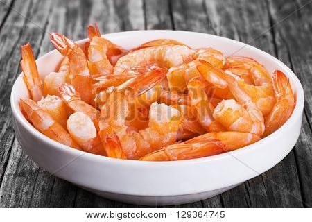boiled tails of king shrimps on a white bowl on an old rustic table close-up studio lights