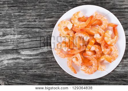 boiled tails of king shrimps on a white dish on an old rustic table blank space left top view studio lights