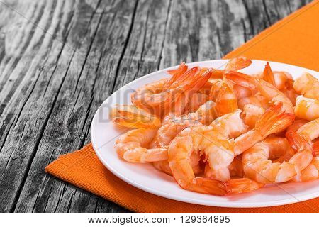 boiled tails of king shrimps on a white bowl on a dish with orange table napkin on an old rustic table close-up studio lights