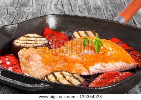 Delicious red fish salmon steak fillet on a iron grill pan with grilled bell pepper and grilled slices of aubergine studio lights close-up