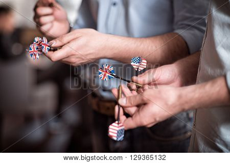 Lets play. Close up of darts in hands of pleasant friends holding them while going to play