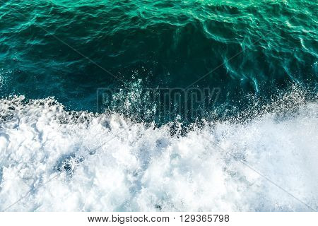 Rolling sea waves top view of ocean covered by foam turquoise and green gradient color water