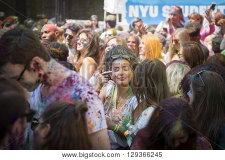 NEW YORK - APR 30 2016: A large crowd with colorful powder on their faces celebrate Holi Hai Festival of Colors and watch performers on the stage hosted by NYC Bhangra in New York on April 30 2016.