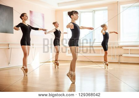 Young dancers is doing exercises in ballet class