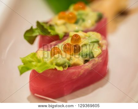 Tuna sushi with avocado sauce and spawn on plate