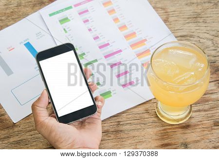 White display Smart phone in hand Cold glass lemonade Graph data analysis placed on wooden floor.