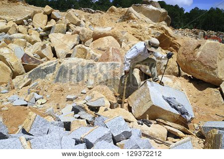 Dalat, Vietnam, September 10, 2015: Worker with splitter on hand try to split stone into rectangle shape for road-works at mountain pass in Lam Dong, Viet Nam