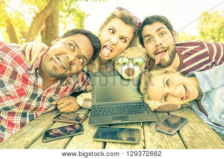 Best friends taking selfie outdoors with back lighting - Happy friendship concept with young people having fun with smartphones and laptop - Warm vintage filtered look and enhanced sunshine halo flare