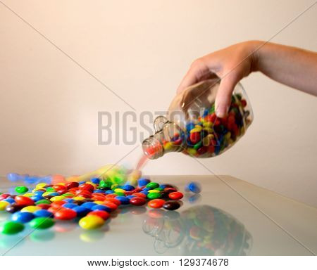Multi-colored candy being poured from a dish.
