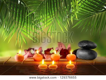 Composition with spa stones and candles on natural blurred background