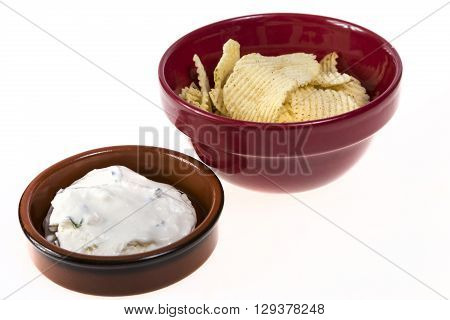 Potato chips and bowl of onion dip isolated on white background.