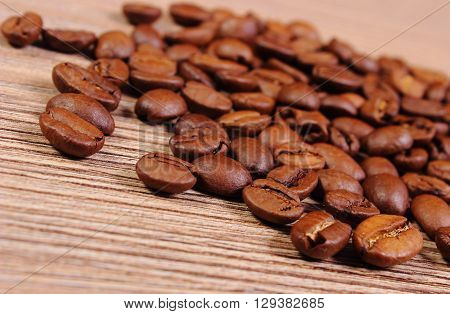 Coffee beans lying on wooden background coffee grains