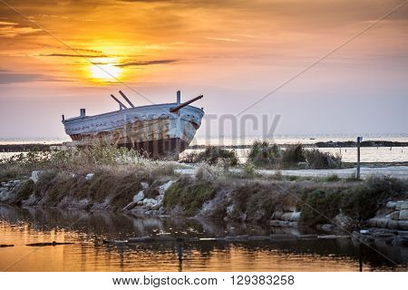 An old and weathered boat at the sicilian sunset