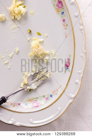 Scraps of cake on almost empty plate with a fork - top view