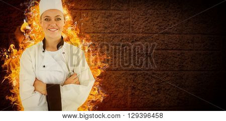 Composite image of woman chef smiling and crossed arms on fire and stone background