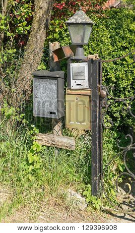 sunny illuminated scenery showing a garden gate with letter boxes doorbell and lamp