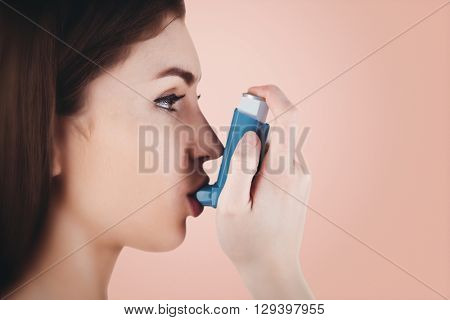 Portrait of an asthmatic woman against orange background
