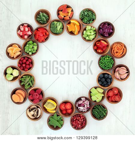 Paleo diet health and super food of fruit and vegetables in wooden bowls forming an abstract wheel over distressed white wood background. High in vitamins, antioxidants, minerals and anthocyanins.