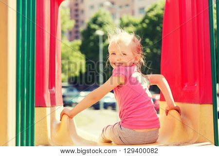 summer, childhood, leisure and people concept - happy little girl on slide at children playground
