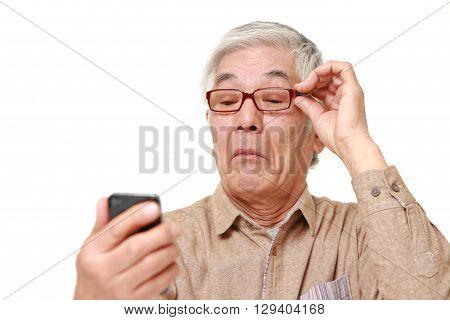 senior Japanese man with presbyopia on white background