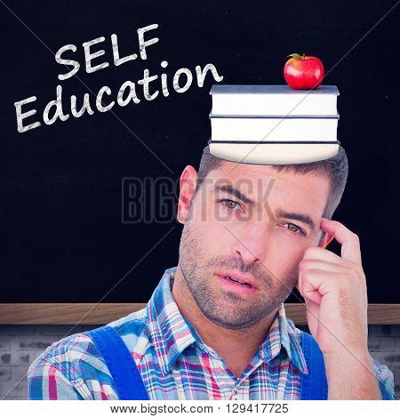 Portrait of confused manual worker scratching head against blackboard on wall