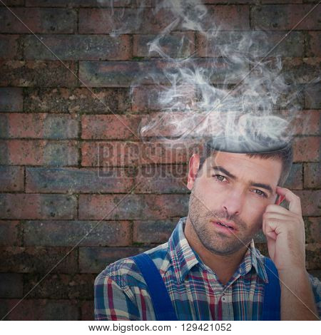 Portrait of confused manual worker scratching head against brick wall