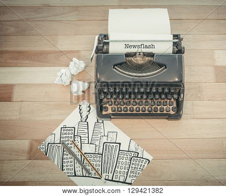 The word newsflash and cityscape with brainstorm doodle against typewriter and paper on table in office