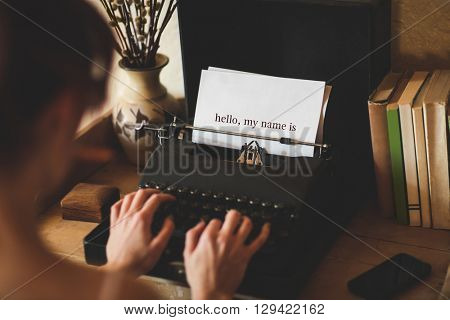 The word hello, my name is against young woman using typewriter