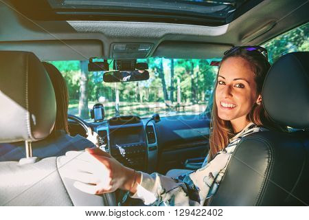Portrait of happy young woman smiling sitting inside of car while her friend driving in a road trip adventure. Female friendship and leisure time concept.