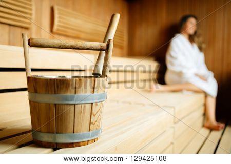 Beautiful woman sitting in finnish sauna and sweating