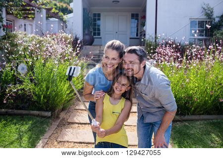 Parents and daughter in garden taking a selfie with selfie stick