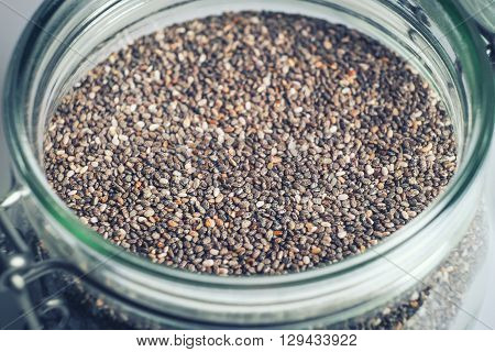 Chia seeds in glass jar extreme macro selective focus. Toned.